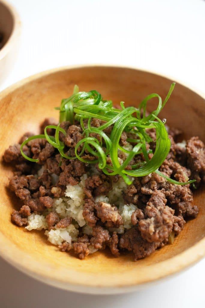 garlic ground beef and cauliflower rice 'caulirice' bowl with green onion garnish