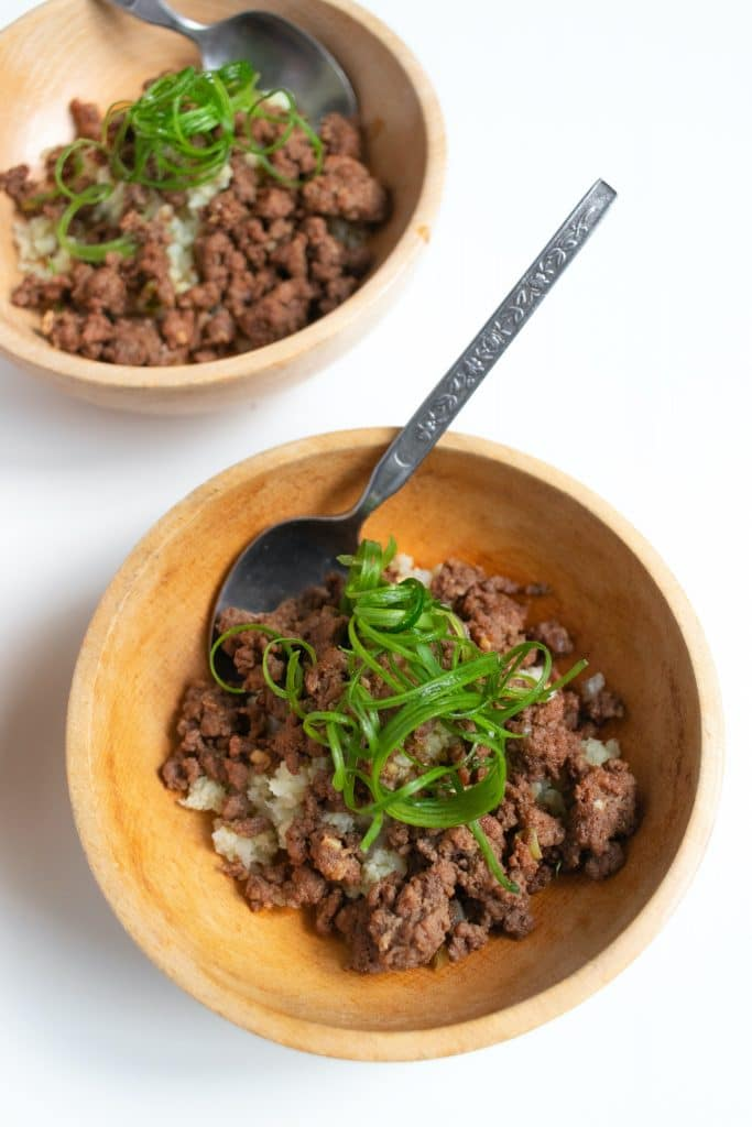 two bowls of low carb garlic beef and cauliflower rice with green onions and spoon for lazy keto meal